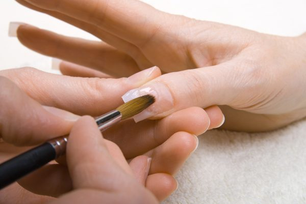 Professional manicurist applying liquid acrylic to nail extensio
